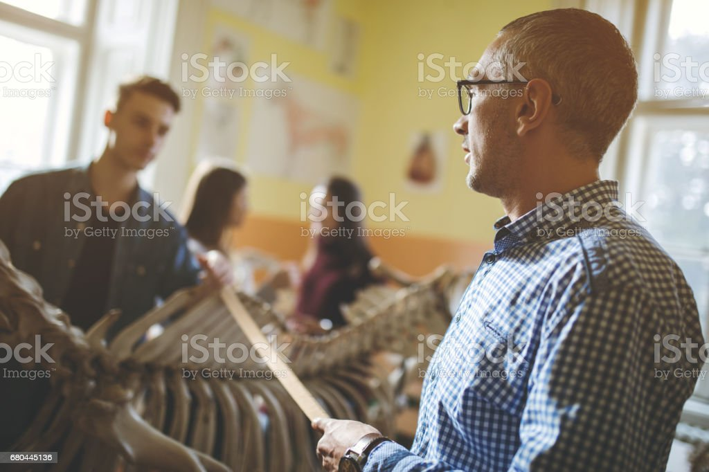 Mid adult high school biology teacher giving a lecture. stock photo