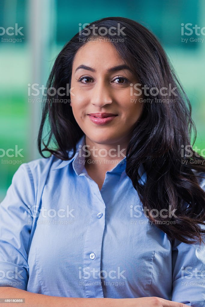 Mid adult Hispanic businesswoman smiling at camera in office stock photo