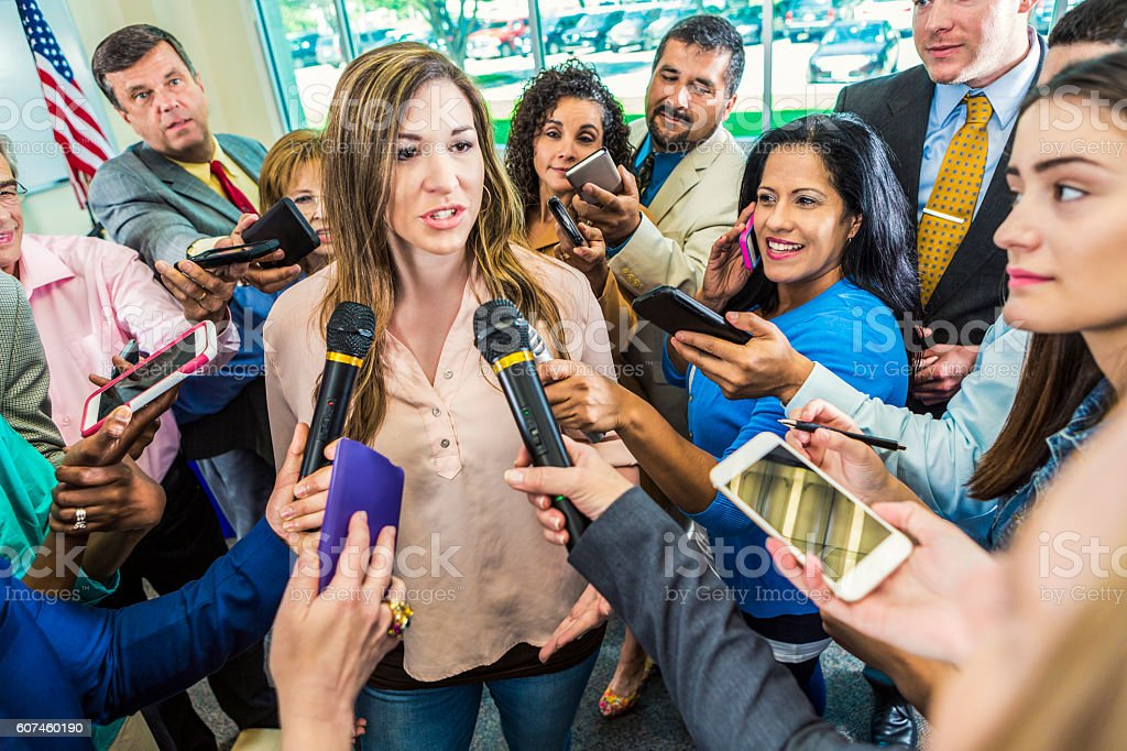Mid adult Hispanic female politician answers questions after her speech stock photo