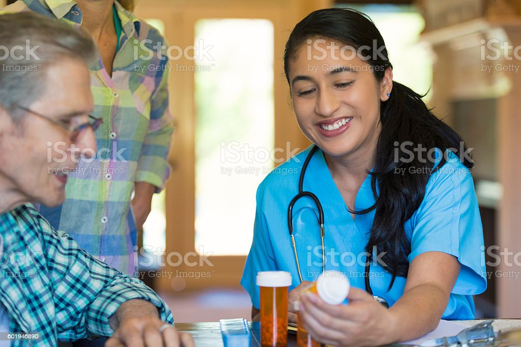 Mid adult Hispanic nurse visits with senior male patient stock photo