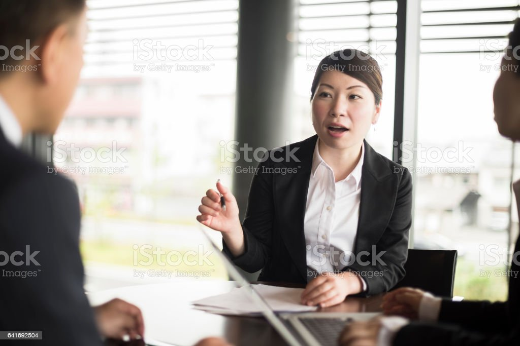 Mid adult Japanese businesswoman gesturing in business meeting stock photo