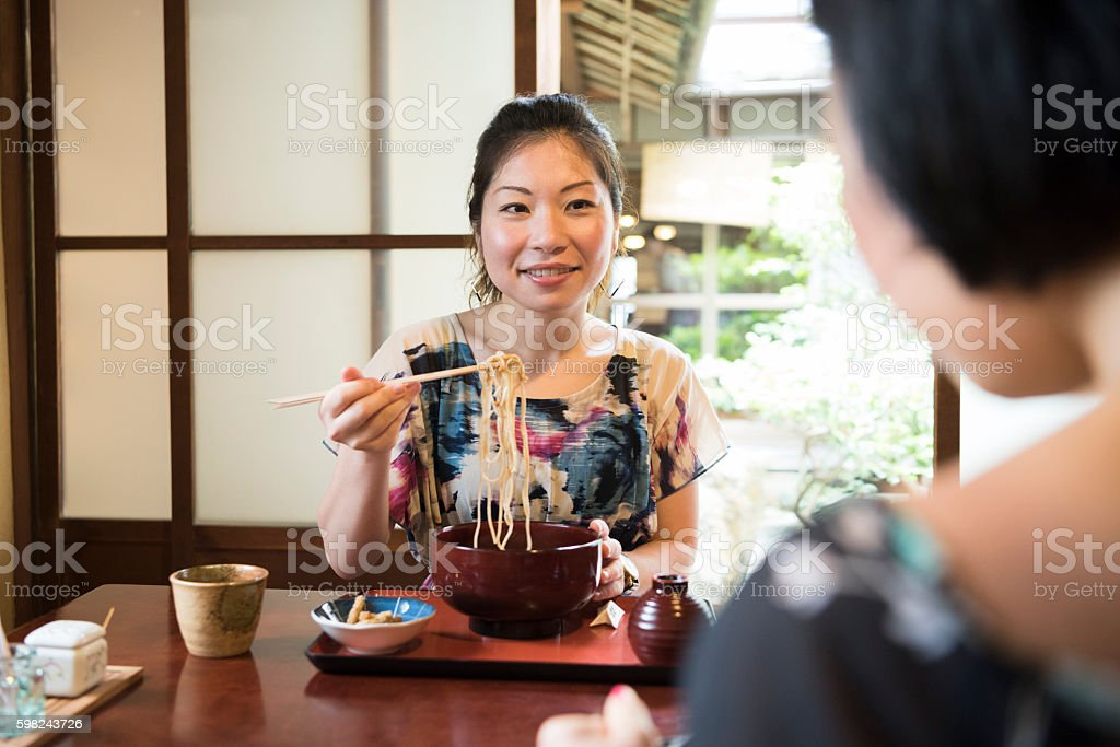 Mid adult Japanese woman eating noodles in restaurant stock photo