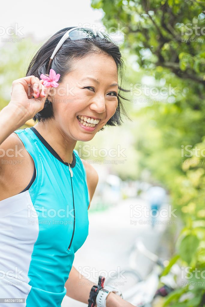Mid Adult Japanese Woman Holding Rhododendron Blossom in Kyoto, Japan stock photo