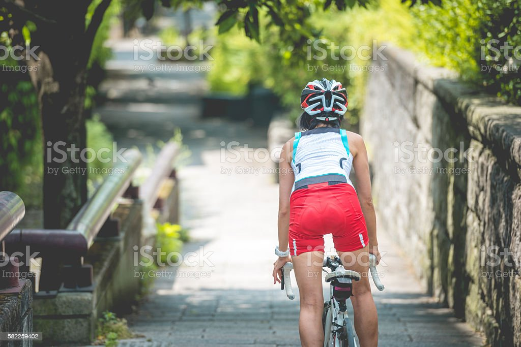 Mid Adult Japanese Woman Riding a Bike in Kyoto, Japan stock photo