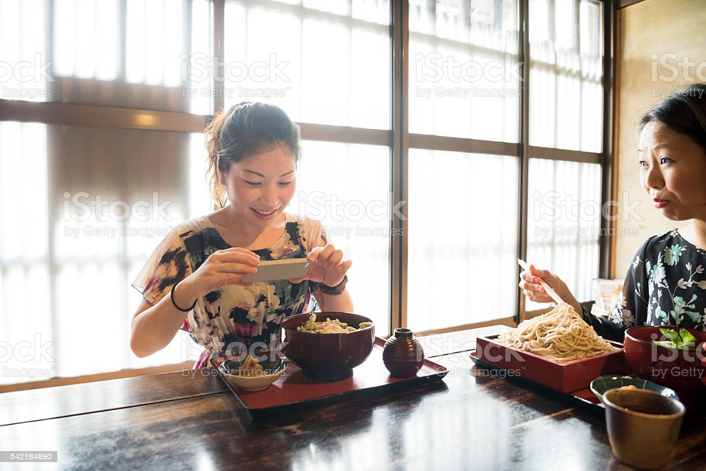Mid adult Japanese woman taking photo of meal in restaurant stock photo