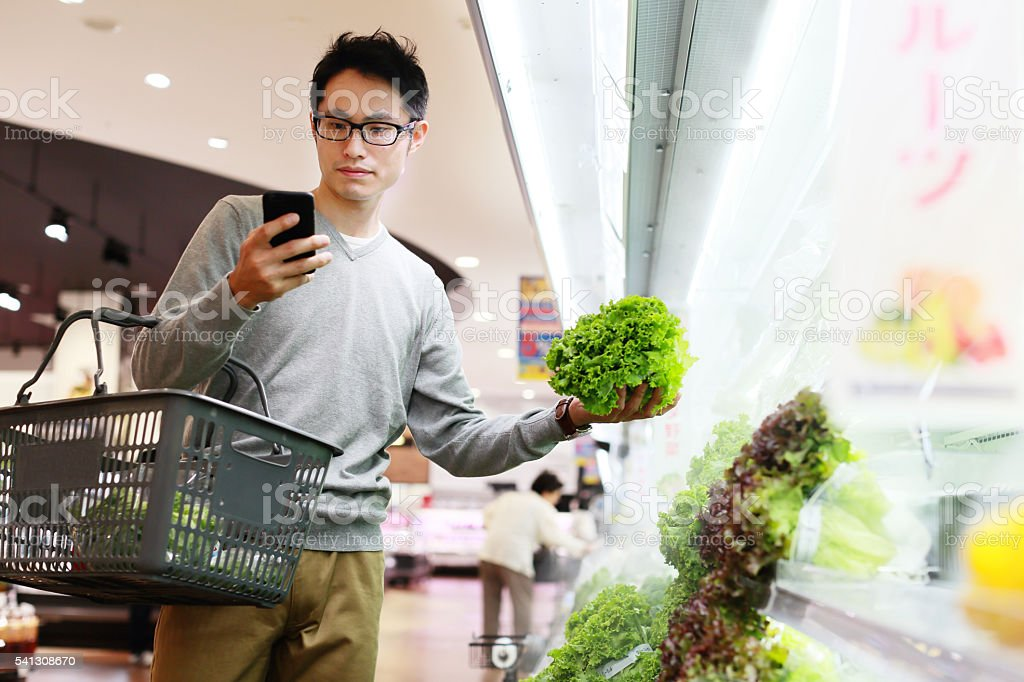 Mid adult male buying grocery in supermarket stock photo