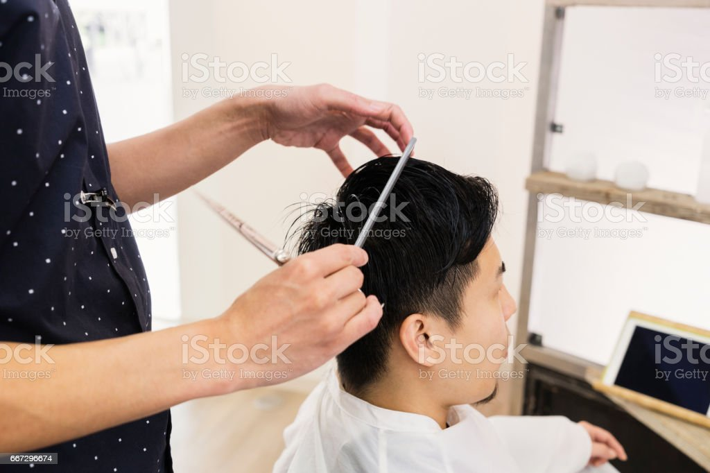 Mid adult male hair salon owner cutting young male's hair. stock photo
