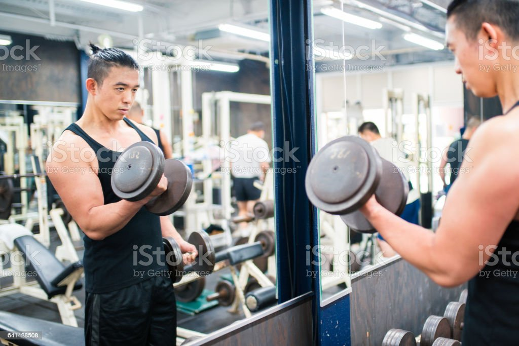 Mid adult male lifting weights stock photo