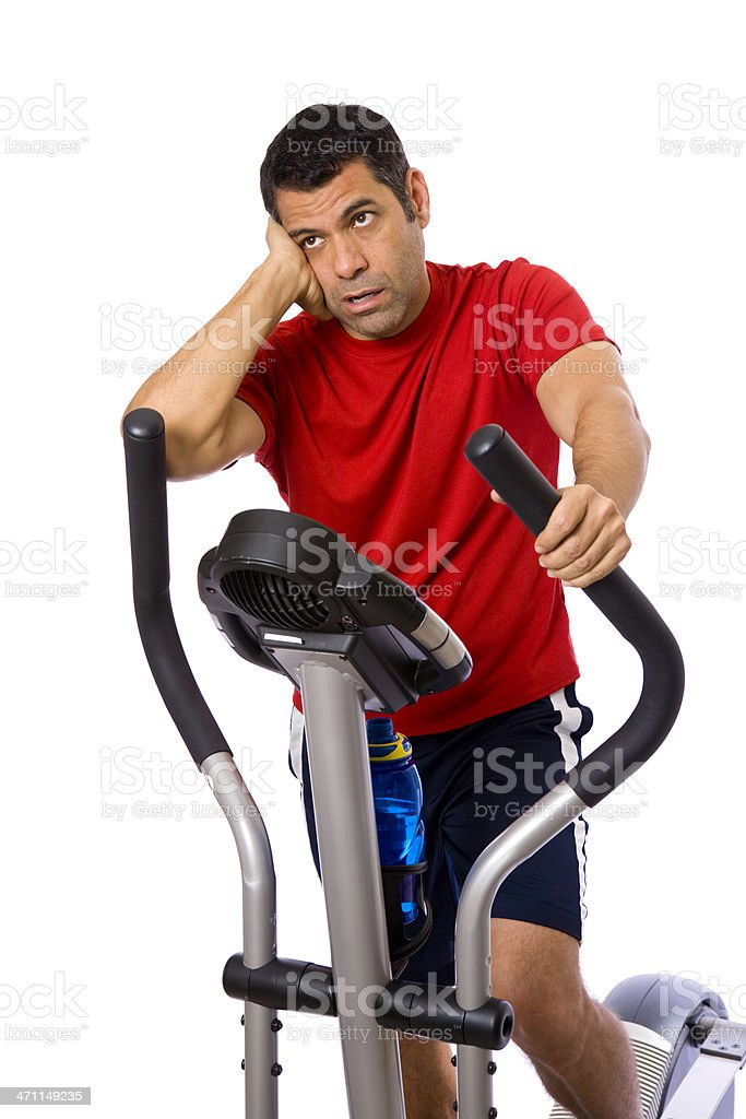 Mid adult male making a face on elliptical machine royalty-free stock photo