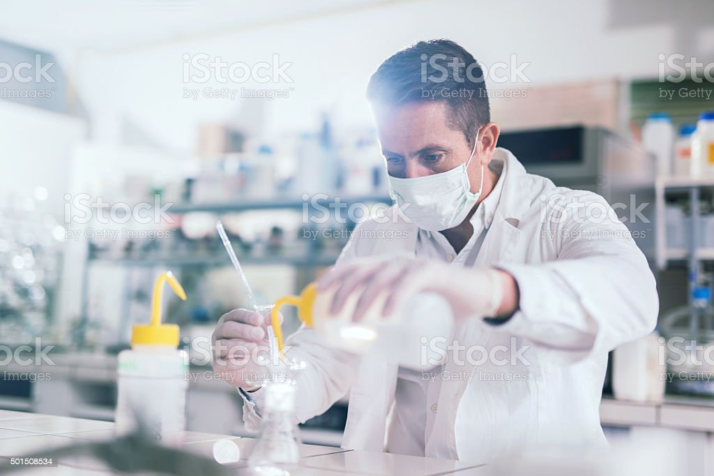 Mid adult male scientist mixing chemical substances for medical research. stock photo