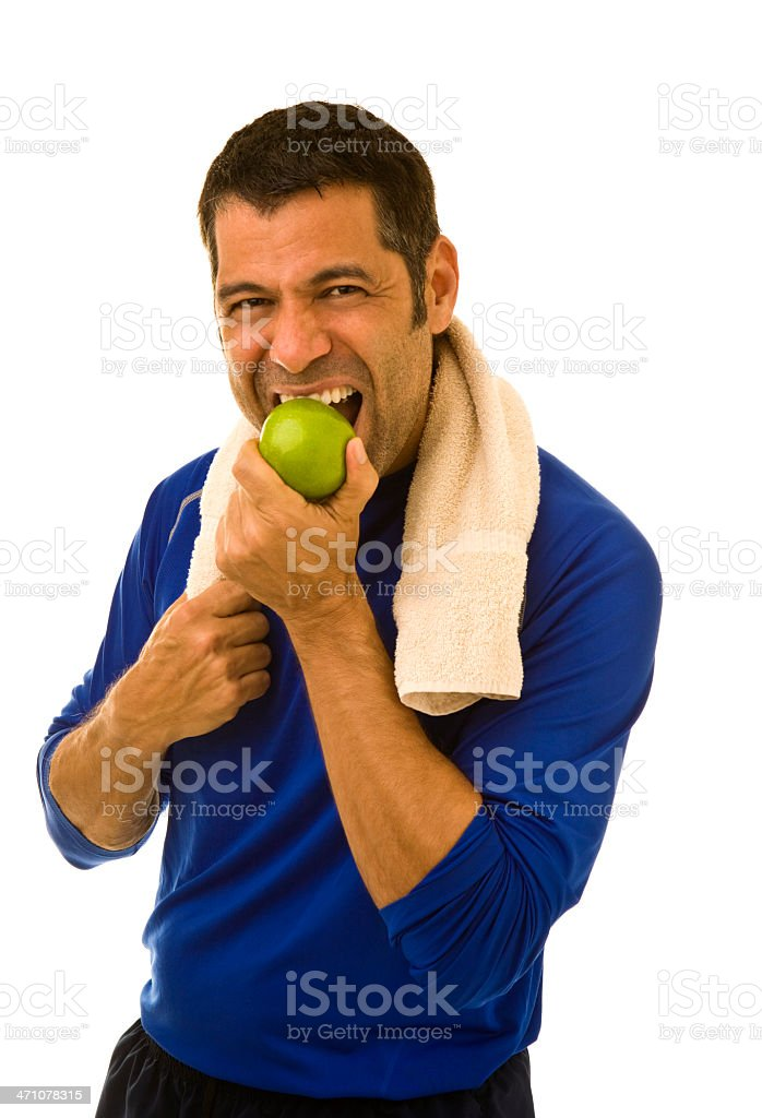Mid adult male wearing workout attire biting into green apple royalty-free stock photo