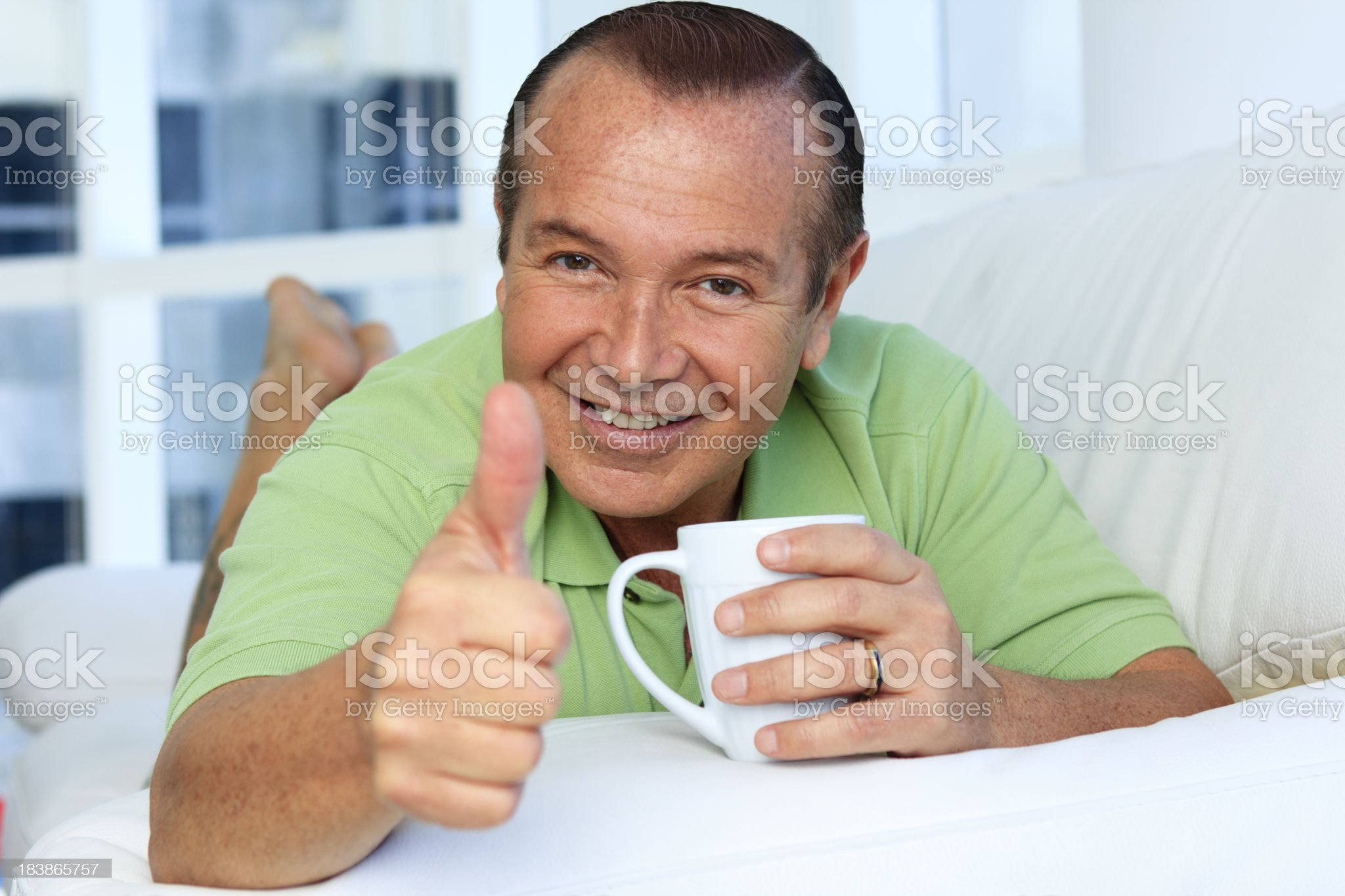 Mid adult male with cup of coffee and thumbs up royalty-free stock photo