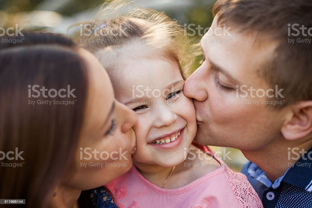 Mid adult man and woman are kissing their little girl stock photo
