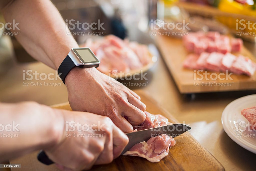 Mid adult man cutting the chicken with a kitchen knife stock photo