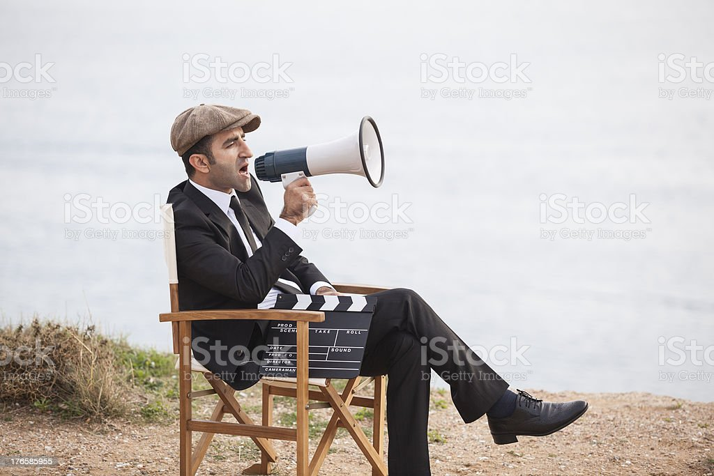 Mid adult man directing film in outdoor set stock photo