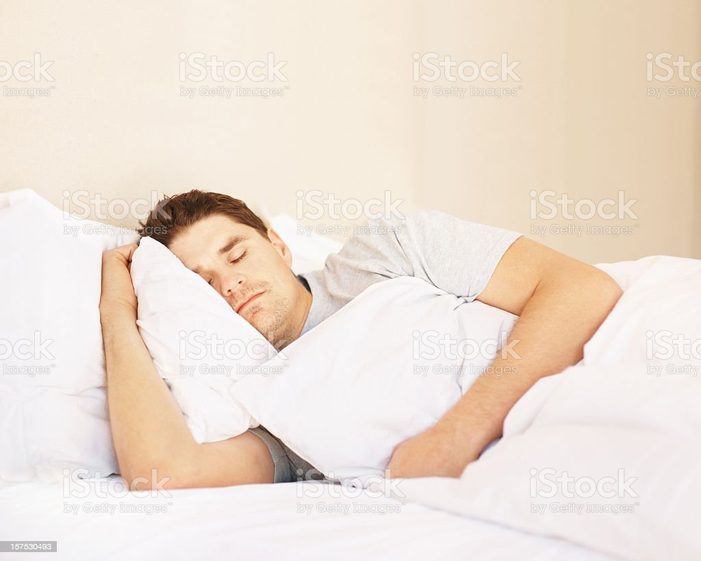 Mid adult man fast asleep in bed royalty-free stock photo