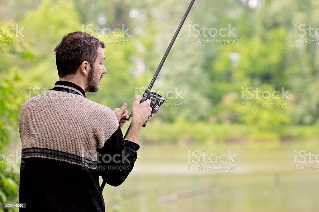 Mid adult man fishing in a pond. stock photo