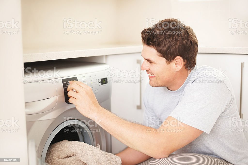 Mid adult man loading clothes into the washing machine stock photo