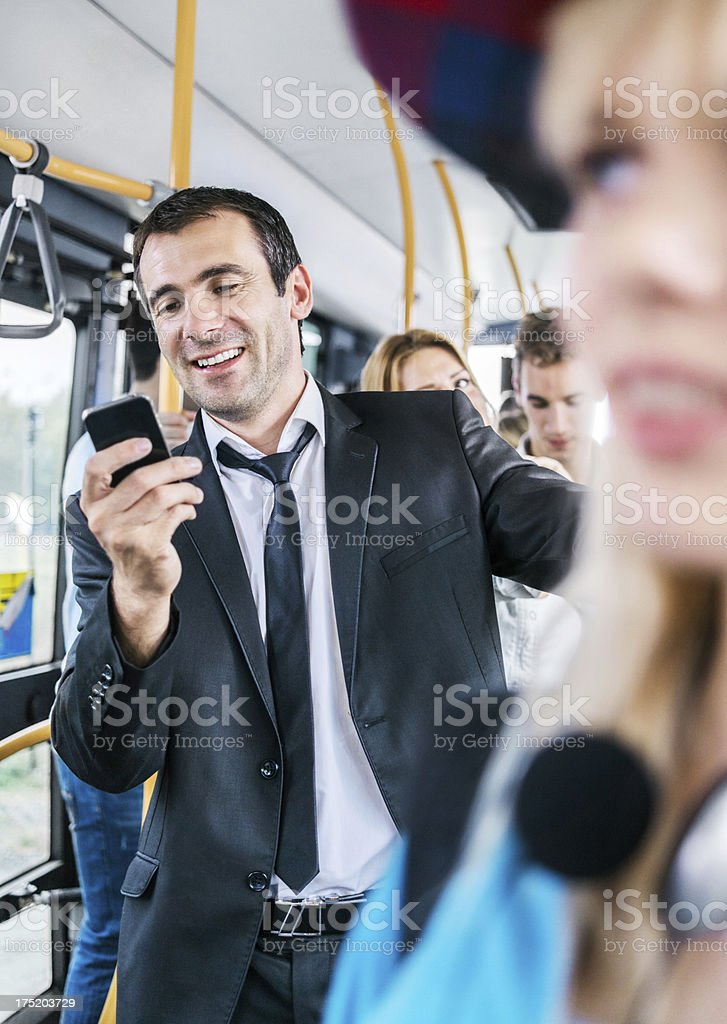 Mid adult man sending text messages while commuting by bus. royalty-free stock photo