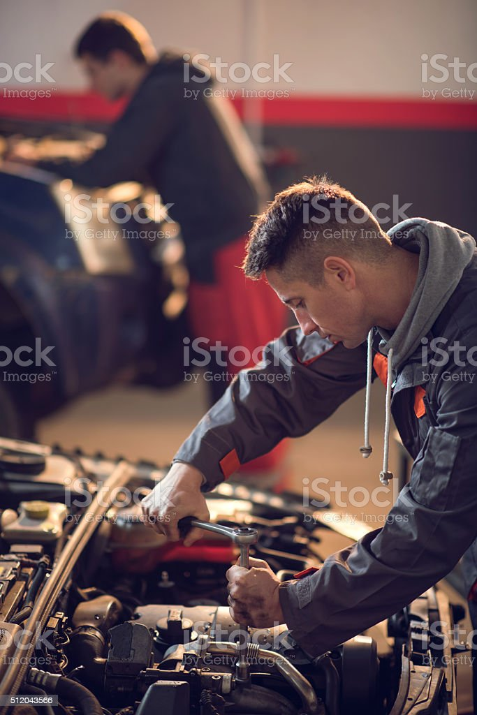 Mid adult mechanic repairing a car in auto repair shop. stock photo
