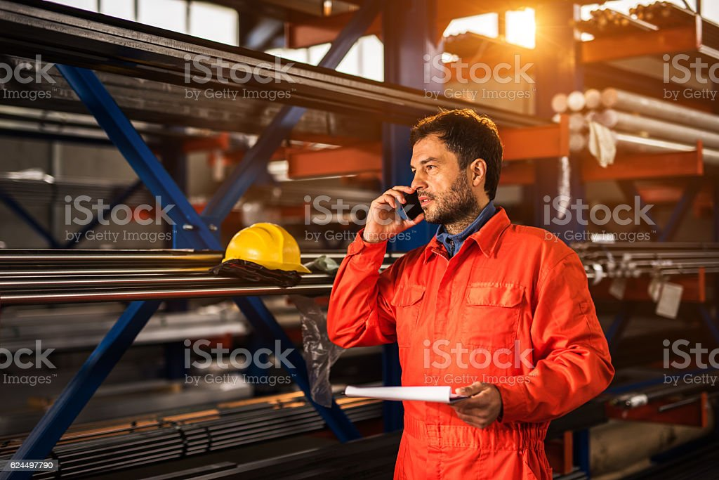 Mid adult metal worker talking on mobile phone in factory. stock photo