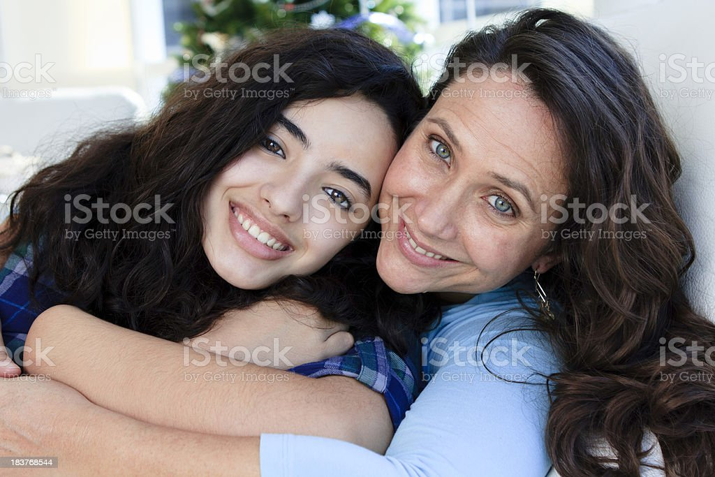 Mid adult mother and teenage daugther embracing royalty-free stock photo