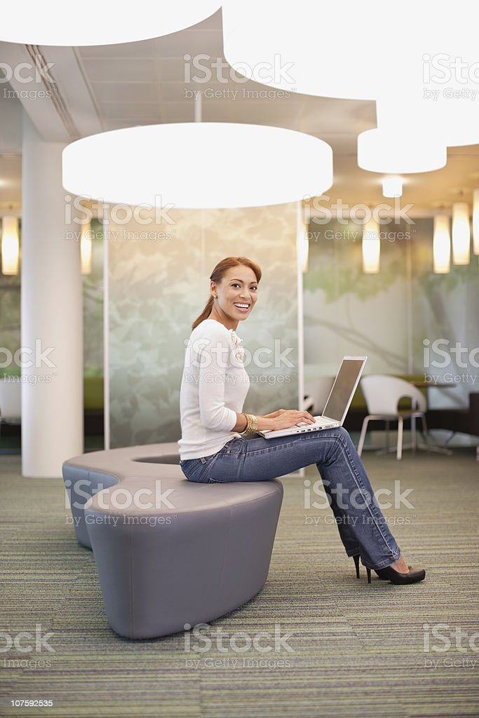 Mid adult office worker using laptop at a modern office canteen royalty-free stock photo