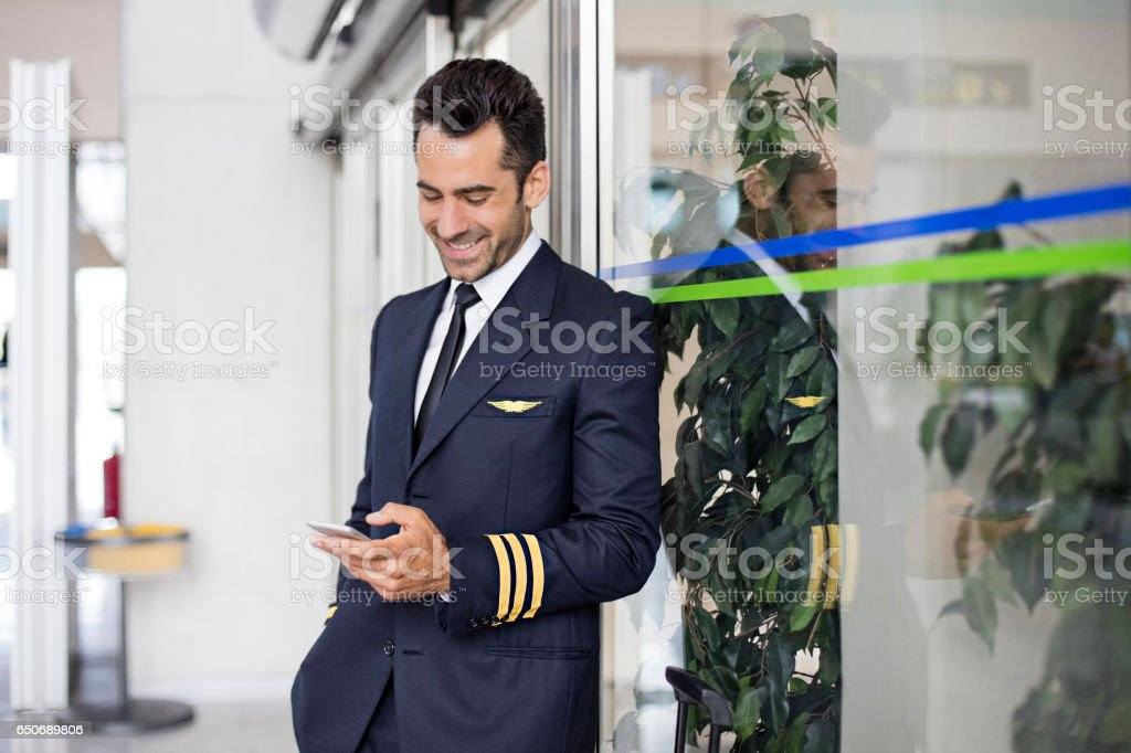 Mid adult pilot using smart phone in airport stock photo