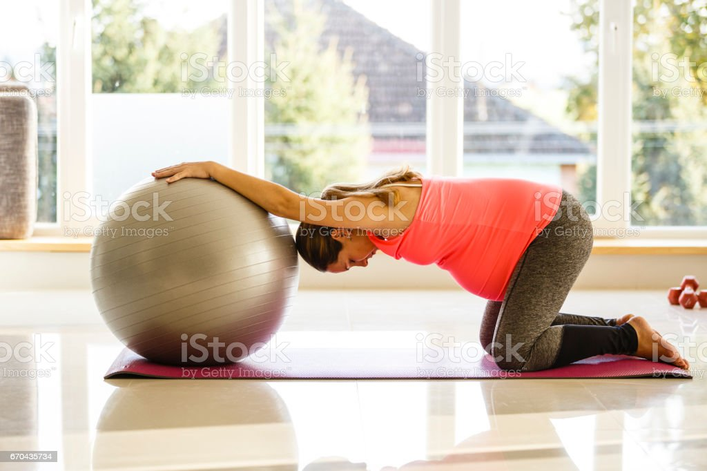 Mid adult pregnant woman is exercising with a ball stock photo