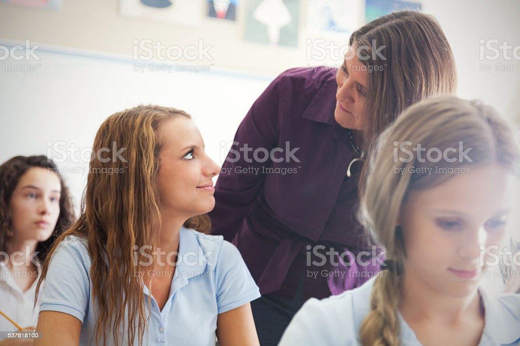 Mid adult teacher helps high school student stock photo