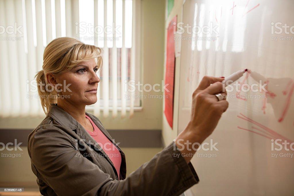 Mid adult teacher writing on whiteboard. stock photo