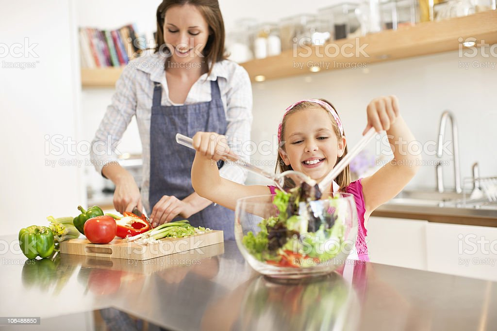 Mid adult woman chopping vegetables while girl (8-9) making salad stock photo
