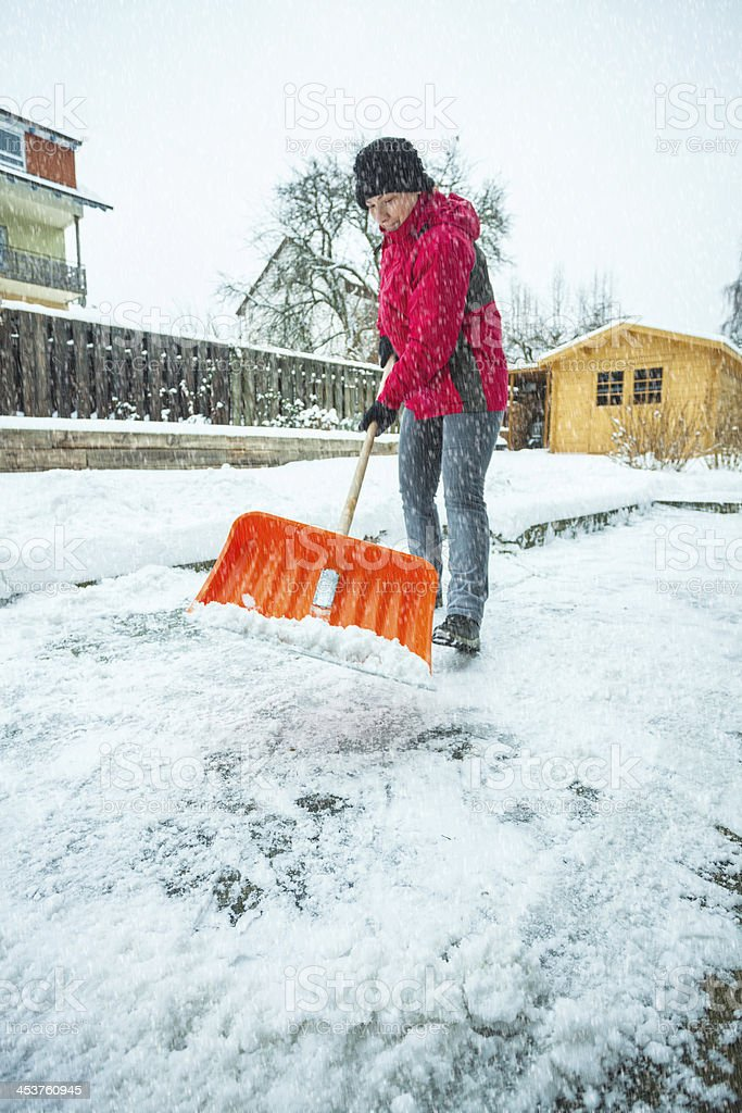 Mid adult woman cleaning snow in front of her house royalty-free stock photo