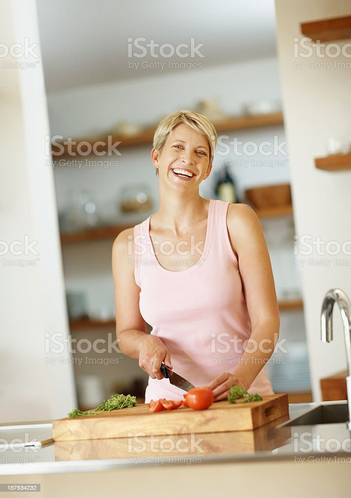 Mid adult woman cutting vegetables in kitchen royalty-free stock photo