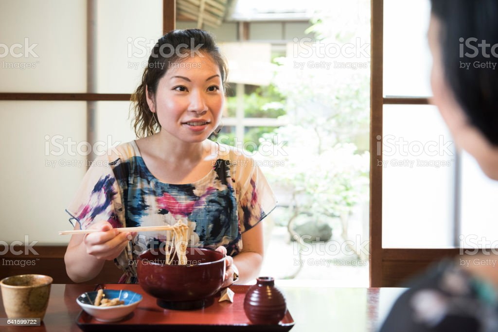 Mid adult woman eating soba noodles in restaurant with chopsticks stock photo