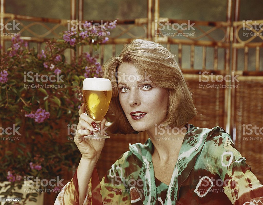 Mid adult woman holding beer glass, portrait, close-up stock photo