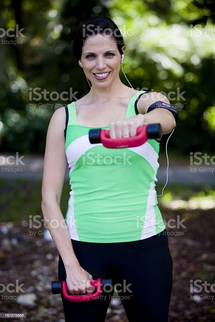 Mid adult woman holding hand weights stock photo