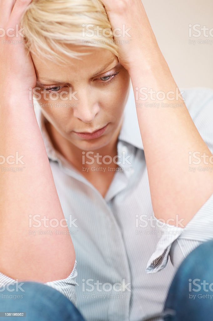 Mid adult woman holding head and sitting royalty-free stock photo