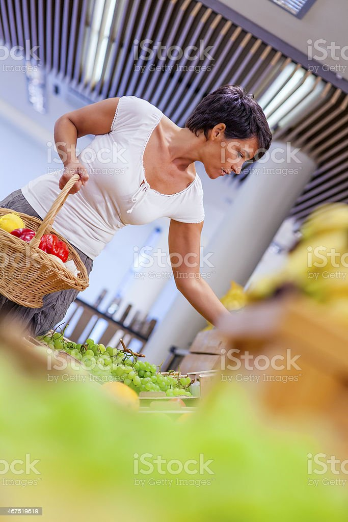 Mid adult woman in greengrocer's shop royalty-free stock photo