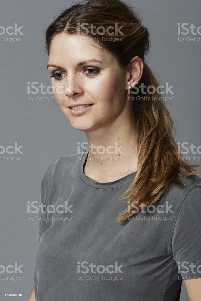 Mid adult woman in grey t-shirt looking away royalty-free stock photo