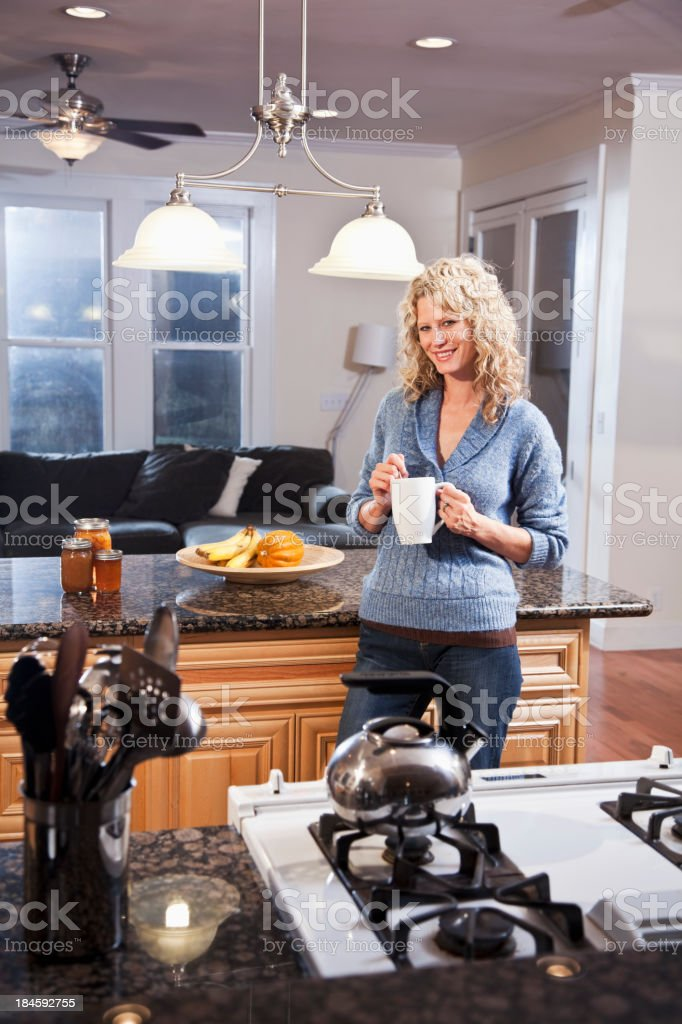 Mid adult woman in kitchen with hot drink stock photo