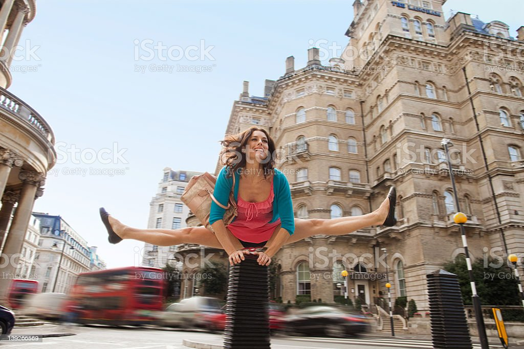 Mid adult woman in pink dress leapfrogging through city street stock photo