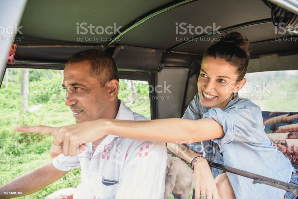 Mid adult woman in rickshaw pointing, man driving stock photo