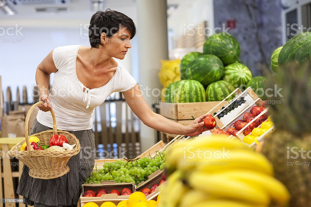 Mid Adult Woman In Supermarket Shopping Groceries stock photo