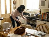 Mid adult woman loading dishwasher