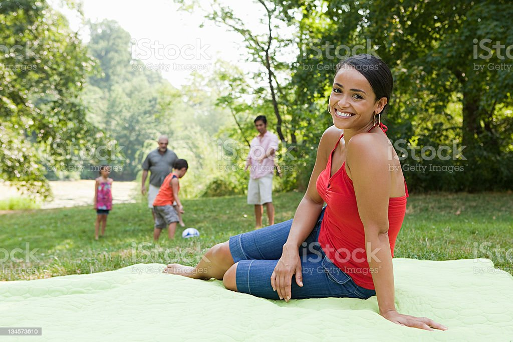 Mid adult woman on blanket in park, portrait stock photo