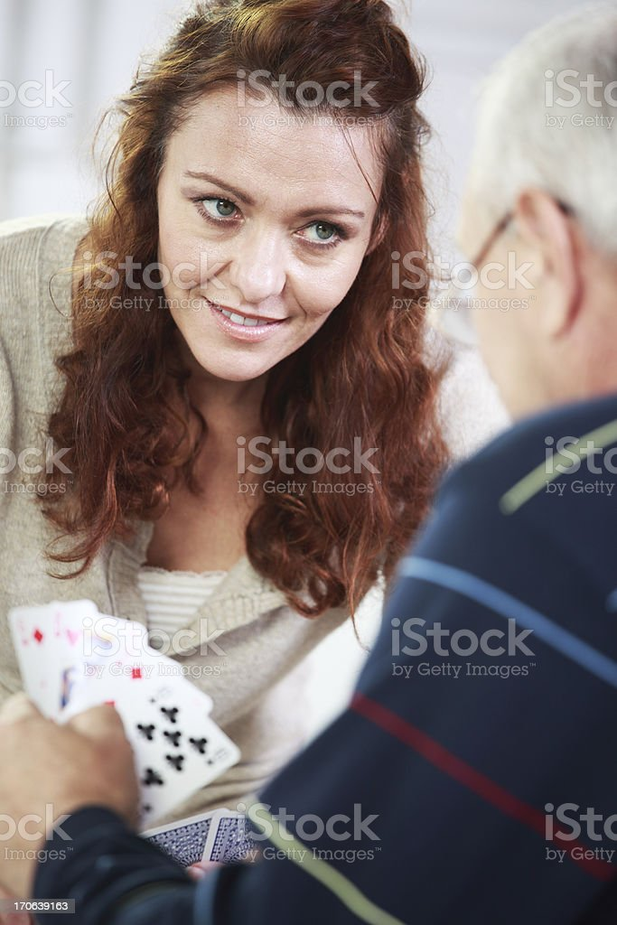 Mid Adult Woman Playing Cards With Her Father stock photo