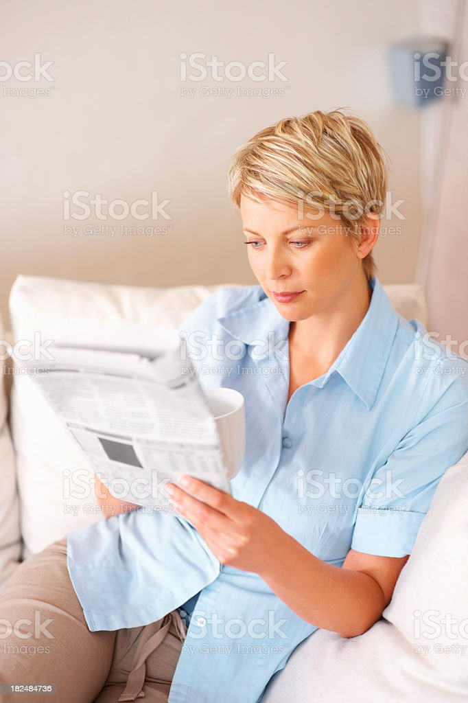 Mid adult woman reading a newspaper royalty-free stock photo