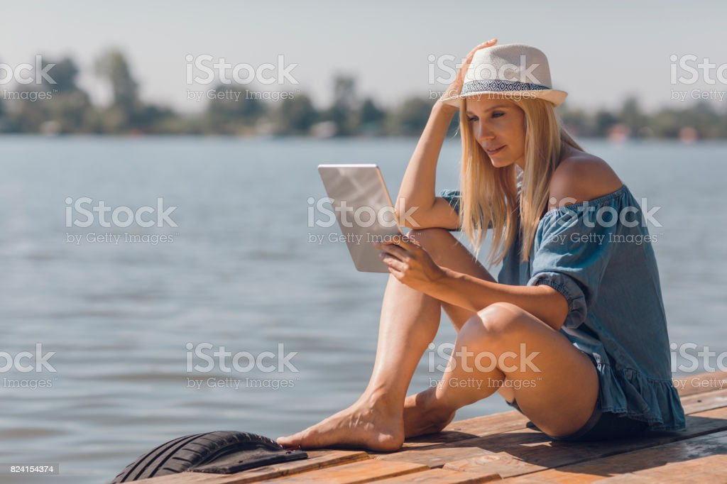 Mid adult woman relaxing by the lake stock photo