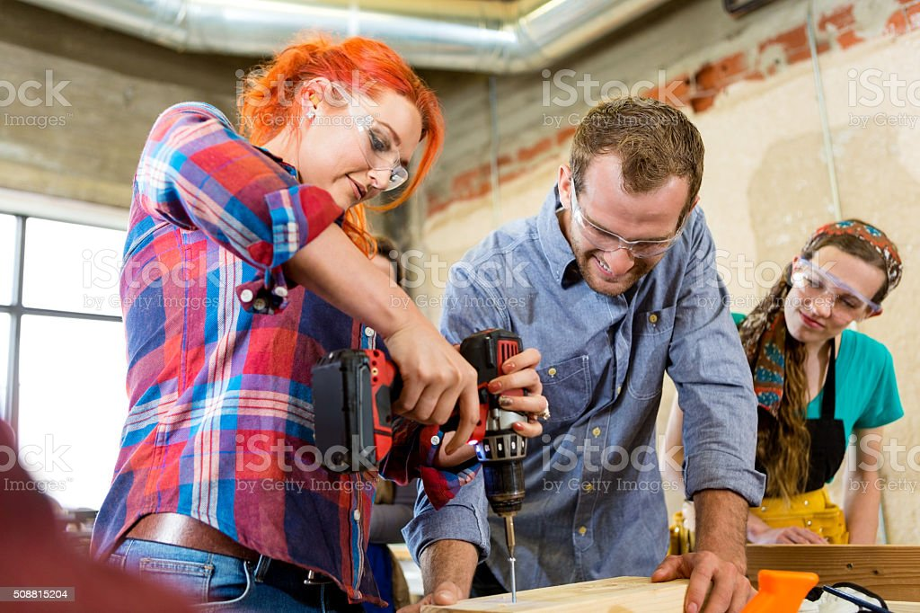 Mid adult woman uses power drill in makerspace stock photo